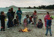 families gather around a campfire on the beach at a homeschooling camp